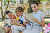 four adorable multicultural friends sitting on bench in schoolyard and reading books