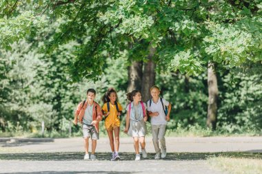 four happy multicultural schoolkids with backpacks running in sunny park