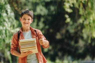 cheerful schoolboy smiling at camera while showing thumb up and holding books