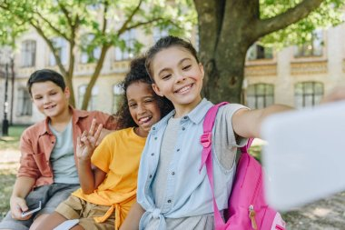 cheerful schoolgirl taking selfie with multicultural friends while sitting on bench in schoolyard