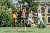 four excited multiethnic schoolkids jumping while holding books on lawn in park