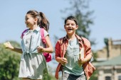 Photo two happy schoolkids with backpacks smiling while running in park