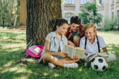 three cute classmates reading book and smiling while sitting on lawn under tree