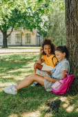 two multicultural schoolgirls reading books while sitting on lawn under tree