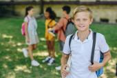 szelektív középpontjában mosolygó iskolás nézi kamera mellett állandó közelében multikulturális barátok
