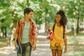 két mosolygó multikulturális iskolás séta a parkban, miközben gördeszkát