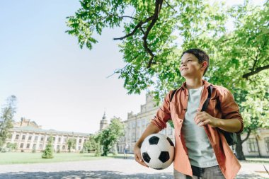 Cute schoolboy with soccer ball walking in park with blue sky and green tree on background stock vector