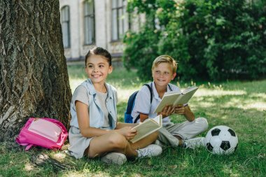 adorable schoolboy and schoolgirl sitting on lawn with books and looking away