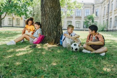 four cute multicultural schoolkids sitting on lawn and tree, speaking and reading books