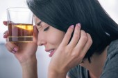 Photo beautiful upset woman with whiskey glass at home
