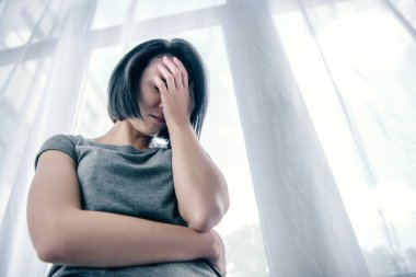 low angle view of depressed woman covering face at home