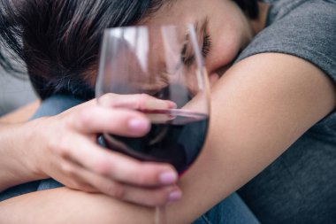 selective focus of depressed woman with wine glass at home