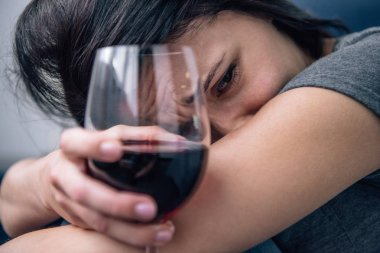selective focus of depressed lonely woman with wine glass at home