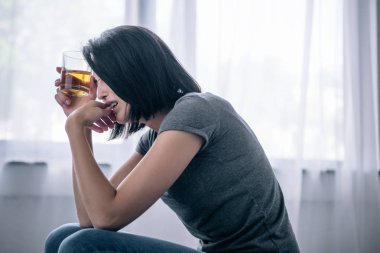 upset lonely woman with whiskey glass at home