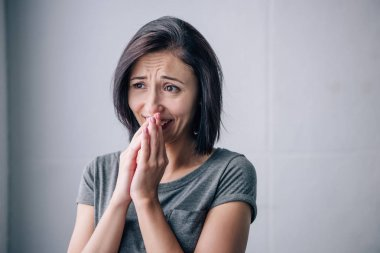 sad brunette woman covering mouth and crying at home