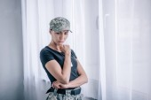 Photo depressed pensive woman in military uniform touching chin at home