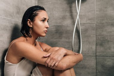 lonely upset woman sitting in shower at home