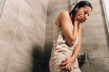 lonely sad woman crying in shower at home with copy space
