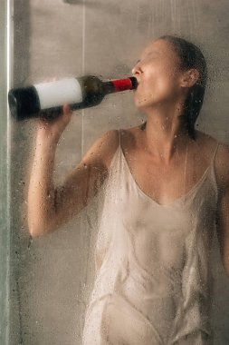 lonely depressed woman in shower drinking wine at home