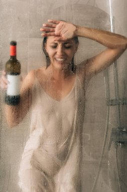 lonely depressed woman holding wine bottle, touching glass door and crying in shower