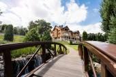 selektiver Fokus der Holzbrücke in der Nähe von grünem Park und Luxushaus