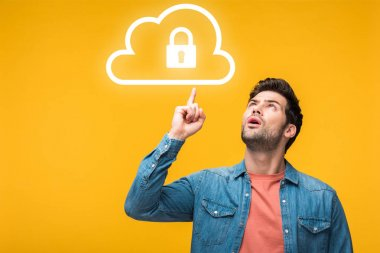 Confused handsome man pointing with finger at internet security icons isolated on yellow stock vector