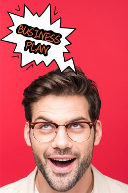 Excited handsome man in glasses looking up at speech bubble illustration with business plan lettering isolated on red stock vector
