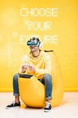 man on bean bag chair in virtual reality headset on yellow with choose your future illustration