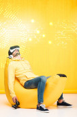KYIV, UKRAINE - APRIL 12: man sleeping on bean bag chair with joystick in virtual reality headset on yellow with cyberspace illustration