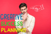 Fotografie pensive man in glasses touching chin isolated on red with creative, success and planning illustration