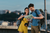 Fotografie handsome man and asian woman smiling and looking at map