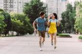 pohledný muž a asijská žena, jak běží a dívá se na sebe