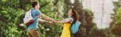 panoráma lövés az ember és az ázsiai nő mosolygott és kézen