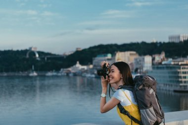 Side view of asian woman with backpack taking photo stock vector