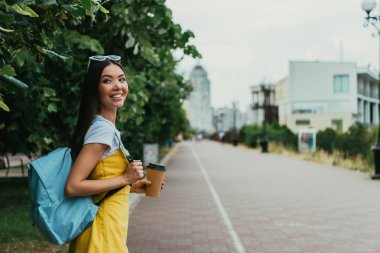 asian woman holding paper cup with coffee and looking away