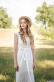 krásná dívka se slamákem a bílými šaty na louce a s pohledem stranou