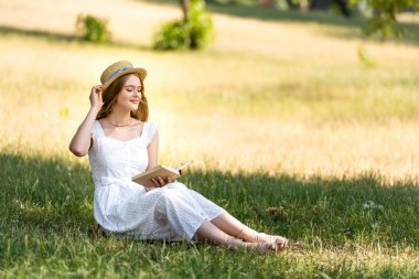 Beautiful girl in white dress touching straw hat and holding book while sitting on meadow with closed eyes stock vector