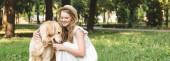 panoráma lövés gyönyörű lány, fehér ruhában, és Szalmakalapot alsószoknya Golden Retriever miközben a réten ülve