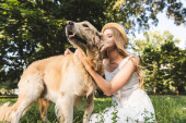 beautiful girl in white dress and straw hat petting golden retriever