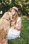 schöne Mädchen in weißem Kleid und Strohhut streichelt Golden Retriever, während sie auf der Wiese sitzt und Hund ansieht