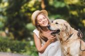 krásná dívka v bílých šatech a slámě seděla poblíž zlatého extraktoru a usmívala se při pohledu na psa