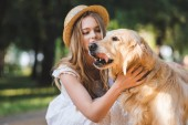 beautiful girl in white dress and straw petting golden retriever and looking at dog