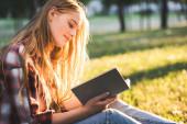 oldalnézetből gyönyörű lány alkalmi ruhák ül réten a napfény és olvasási könyv