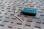 eszközkészlet a kalapács közelében és mérőszalag a tetőn