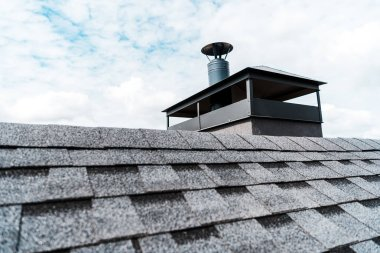 Selective focus of modern chimney on rooftop of house stock vector