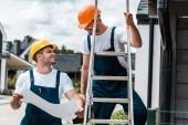 happy builder looking at coworker in helmet standing on ladder