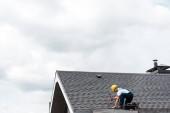 opravník v helmě přidržování kladiva při opravě střechy