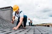 selektivní zaměření handmana přidržování kladiva při opravě střechy u spolupracovníka
