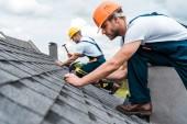 selektivní zaměření pohledného handmana oprava střechy se spolupracovníkem