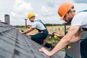 selektivní zaměření pohledného handmana oprava střechy s kolegou